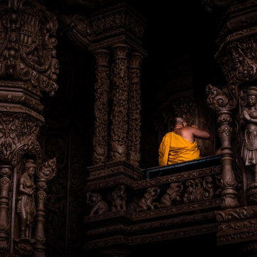 A monk sitting on one of the balconies at The Sanctuary of Truth in Thailand